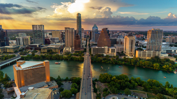 Aerial view of the Austin Skyline as bat watchers and tourist fill the Congress Avenue Bridge to watch the bats take flight as water craft gather on Lady Bird Lake to watch the nightly bat spectacle.