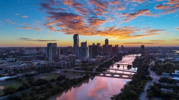 Bird's eye view of the Austin Skyline and bridges over Lady Bird Lake connecting north and South Austin during a beautiful red sunrise.